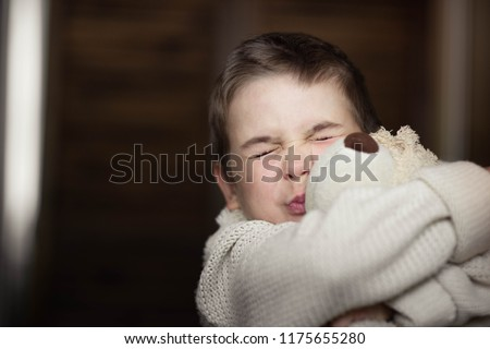 Portrait, a young boy in a white sweater hugs his favorite teddy bear toy, sincere emotions of joy, a smile of happiness on the face of the child. #1175655280