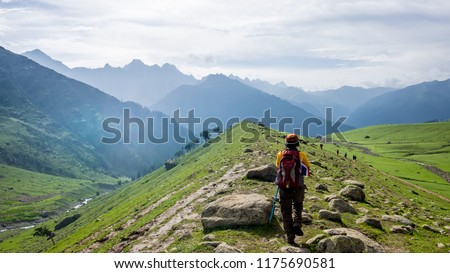 A trekker walks past Gadsar lake and a meadow at kashmir great lakes trek in kashmir. Solo person in the mountains and lake of Kashmir, India. The breathtaking view of Krishansar lake on blue sky. Royalty-Free Stock Photo #1175690581