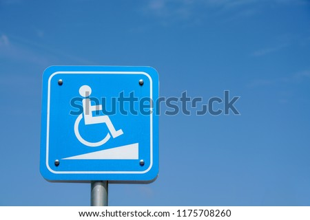 Handicap facility sign on blue signage. Concept for new building and modern architecture.
