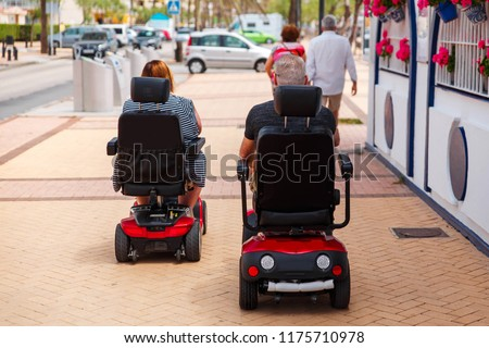 Couple elderly people ride along the sidewalk to an electric wheelchair. Motorized wheelchair. Mobile scooter. #1175710978