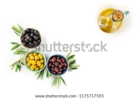 An overhead photo of various olives in bowls with leaves and a cruet of olive oil, with copy space, on a white background #1175717593
