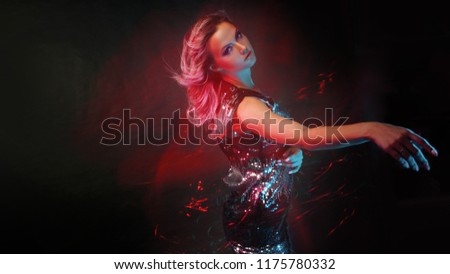 Bright and stylish young woman dancing in club, color light, motion effects. Black background, long exposure #1175780332