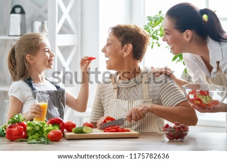 Healthy food at home. Happy family in the kitchen. Grandma, mother and child daughter are preparing the vegetables and fruit. #1175782636