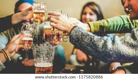 Happy friends cheering with half pints beer in pub restaurant - Young people having fun at chalet bar party - Youth, vacation and nightlife lifestyle concept - Focus on close-up hands #1175820886