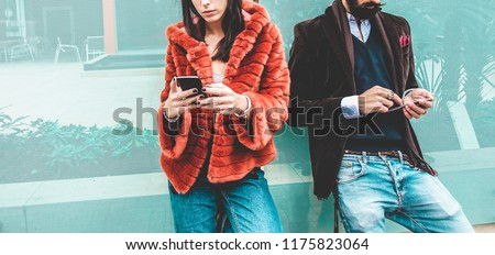 Trendy influencers people using smartphone social media app - Young fashion couple watching story video on mobile cell phone - Technology trends, marketing and new digital job concept - Focus on hands #1175823064