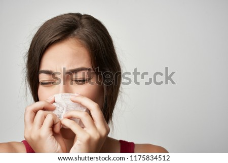 a woman is flogging into a handkerchief on a gray background                                #1175834512