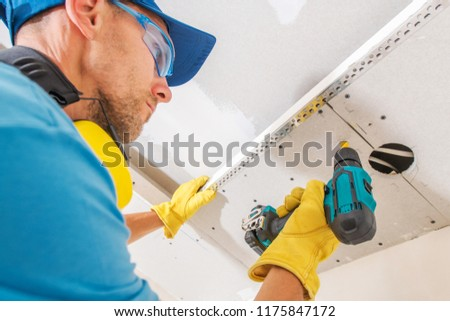 Drywall Ceiling Construction. Caucasian Contractor Worker with Power Tool Building Drywall Elements. #1175847172