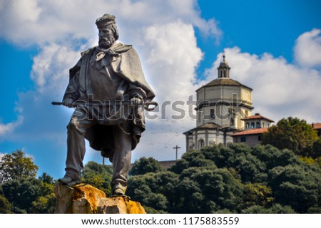 "A statue of Giuseppe Garibaldi, an Italian national hero involved in the Italian unification in the 1800s. The statue is placed in Turin, Italy. In the background, the ""monte dei cappuccini"" church. Royalty-Free Stock Photo #1175883559"