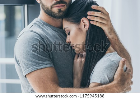 cropped shot of bearded man hugging and supporting young sad woman Royalty-Free Stock Photo #1175945188