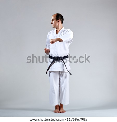 On a gray background, an adult athlete trains formal karate exercises #1175967985