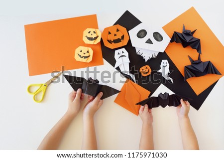 Paper toys of origami for Halloween. Hands of kids. Lesson of origami. Preparation for a holiday. #1175971030