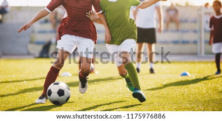 Boys Play Football. Running Football Soccer Players. Kids at Soccer Field Running with Ball. An Action Sport Picture of a Group of Children Playing Soccer Football Game #1175976886