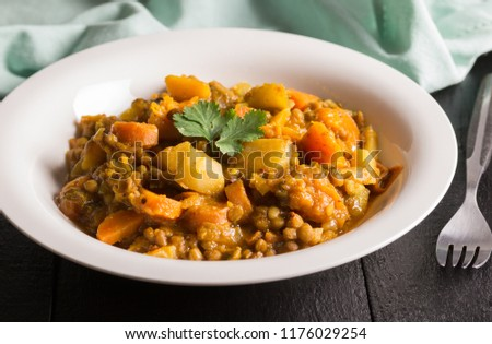 Lentil curry in a plate close up - Vegan recipe consisting of lentils, celery, carrot, potatoes and spices #1176029254