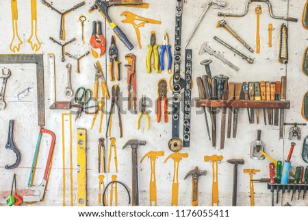 Many different rusty old tools hanging on a wall #1176055411