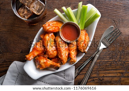 A serving of delicious spicy buffalo chicken wings on a pub style restaurant table top. Royalty-Free Stock Photo #1176069616