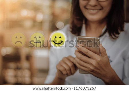 Businesswoman pressing face emoticon on virtual touch screen at smartphone .Customer service evaluation concept. #1176073267