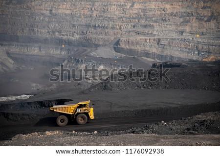 Big yellow mining truck hauling rock in dusty coal mine  #1176092938