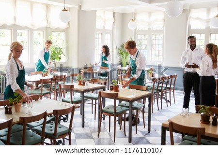 Staff Laying Tables In Empty Restaurant #1176110107