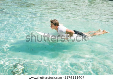 The surfer trains in a quiet azure lagoon. Waiting for the wave. Rowing on the surfboard #1176111409