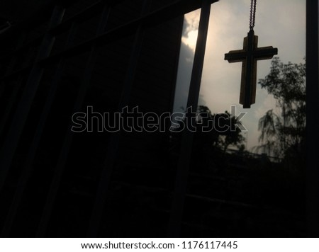 Closeup view of dark silhouette of Jesus christian cross necklace hanging line, loving of God concept picture