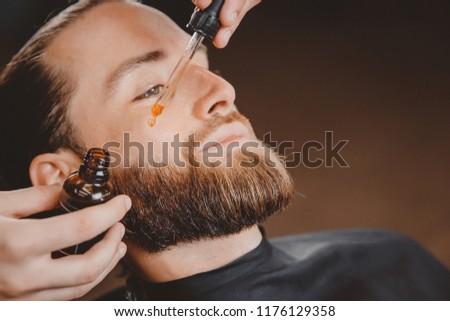 Oil for beard in dropper, process of moisturizing hair. #1176129358