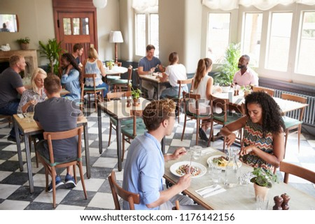 Customers Enjoying Meals In Busy Restaurant #1176142156