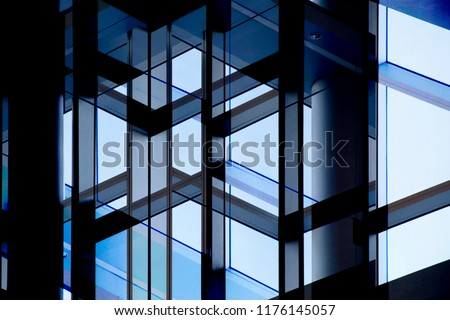 Abstract modern architecture background. Multiple exposure photo of office building windows against clear blue sky. Structural glazing. Glass wall with steel or aluminum framework.