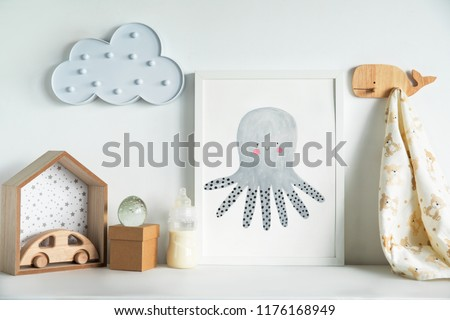 The modern sandinavian newborn baby room with mock up poster frame, wooden car, boxes and clouds. Minimalistic and cozy interior with white walls. #1176168949
