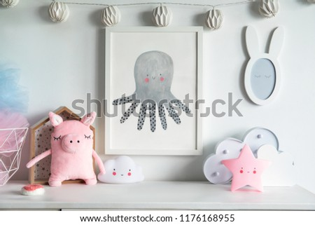 Stylish scandinavian nursery interior with mock up photo frame , pinky pig, toys and star. Hanging cotton lamps and mirror on the white background wall.