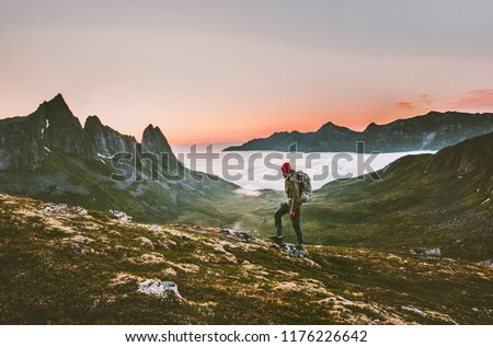 Man backpacker hiking in mountains alone  outdoor active lifestyle travel adventure vacations sunset Norway landscape #1176226642