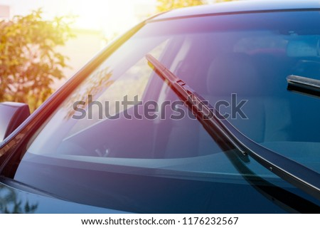 Brushes on the car glass with copy space. The work of windshield wipers - brushes and an evening sunbeam Royalty-Free Stock Photo #1176232567
