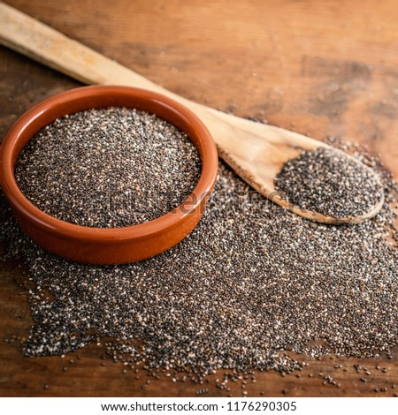 Chia seeds in a clay bowl and  wooden spoon on wood background.   Copy space.