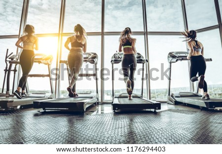 Full lenght of women working out at a gym.Shot of four women jogging on treadmill at gym.  #1176294403