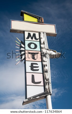 A colorful abandoned Motorlodge motel vintage sign  under a bright blue sky #117634864
