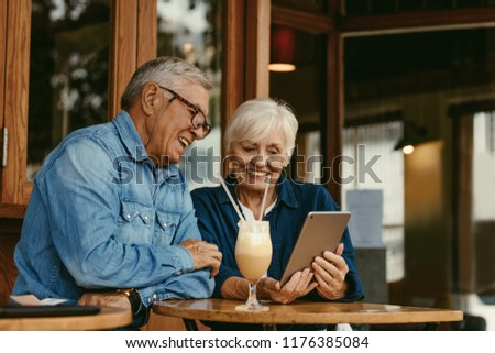 Cheerful senior couple sitting at cafe table and looking at digital tablet. Senior man and woman sitting at coffee shop using tablet pc. #1176385084