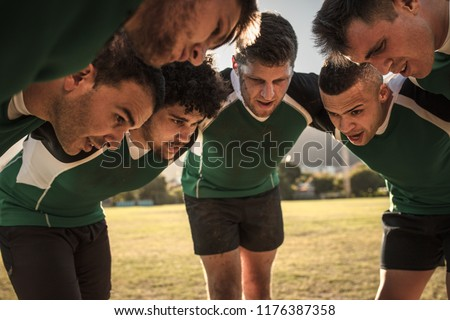 Team of rugby players in huddle discussing their tactics. Professional rugby team in huddle during the game. #1176387358