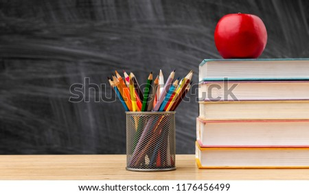 Back to school background with books and apple over blackboard #1176456499