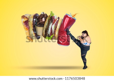 Picture of strong fat woman kicking soft drink and fast food. Shot with yellow background