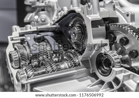 Automobile car gearbox with toothed wheels. Inside view on gearbox cross section with gears and shafts. Car gearbox with open hood cover. #1176506992