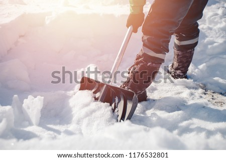 City service cleaning snow winter with shovel after snowstorm yard. sunlight