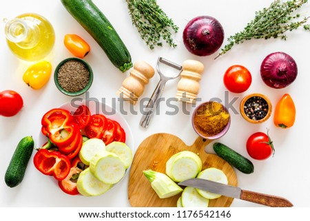 Cooking vegetable stew concept. Fresh vegetables squash, bell pepper, tomato, spices and cutting doard on white background top view #1176542146