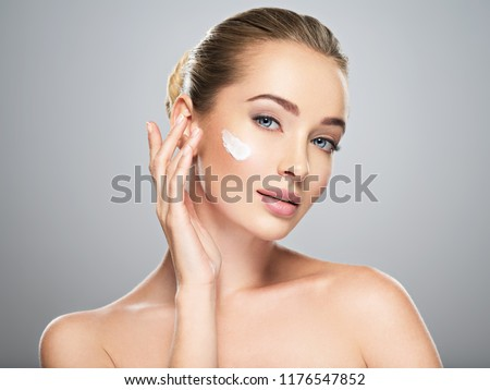 Beautiful young woman gets cream in the face. Skin care concept. Stunning caucasian woman with perfect health clean skin. Portrait of an Attractive girl  with blue eyes, closeup.  #1176547852