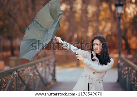 Girl Fighting The Wind Holding Umbrella Raining Weather. Autumn woman having problems in windy storm  #1176549070