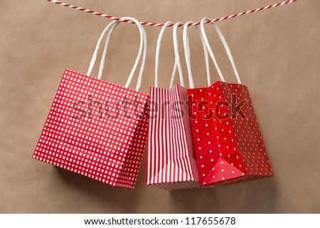 Red gift package paper bags hanging on a ribbon. Old brown paper background #117655678