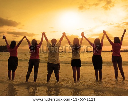Six women hold hands together over their heads together. By the sea at sunset. #1176591121