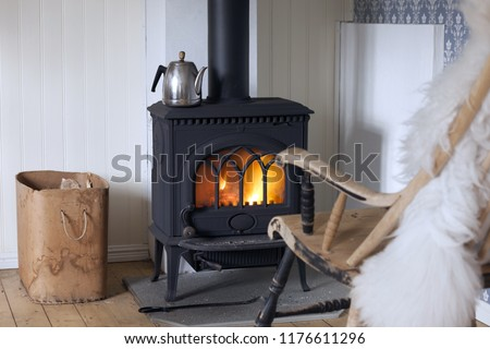Scandinavian interior: wood burning stove, box of firewood and old restored rocking chair in living room corner. Metal coffeepot at stove. White sheep skin in rocking chair. #1176611296