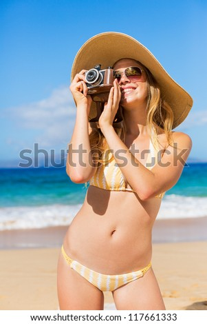 Beautiful Young Woman at the Beach with Vintage Camera #117661333