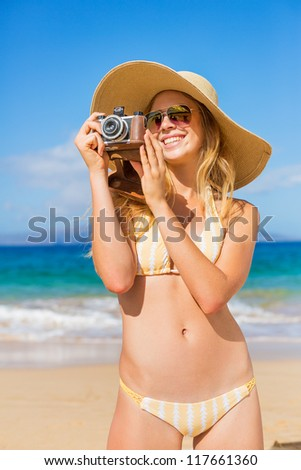 Beautiful Young Woman at the Beach with Vintage Camera #117661360