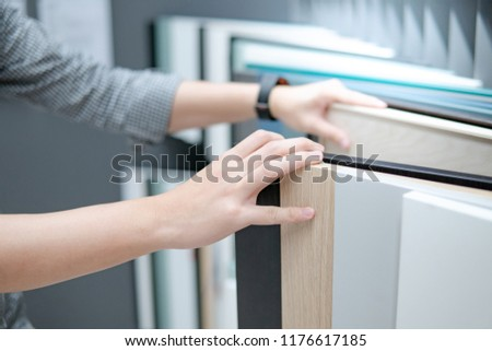 Male hand choosing cabinet panel materials or countertops for built-in furniture design. Shopping furniture and decoration. Home improvement concept #1176617185