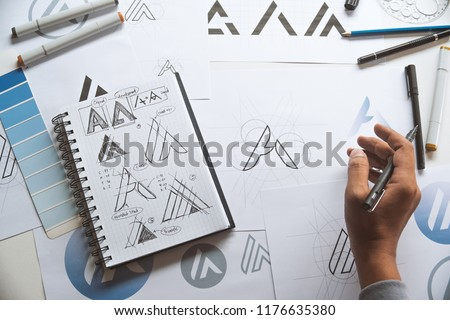 Graphic designer drawing sketch design creative Ideas draft Logo product trademark label brand artwork. Graphic designer studio Concept. #1176635380